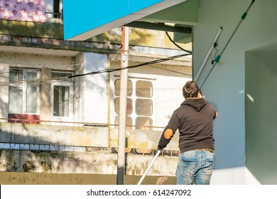 Man with a mop cleans wall