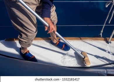 A man mops the deck of a yacht