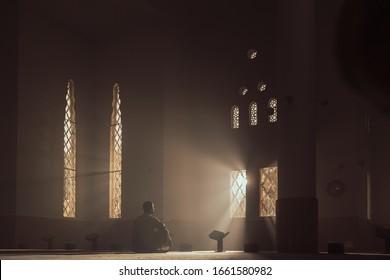 a man in a mosque reads the Qur'an an Arab in a white Kandur Arabic clothing outdoor Qur'an mosque night reading of the Qur'an Ramadan Islam religion Islam