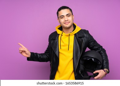 Man with a motorcycle helmet isolated on purple background pointing finger to the side