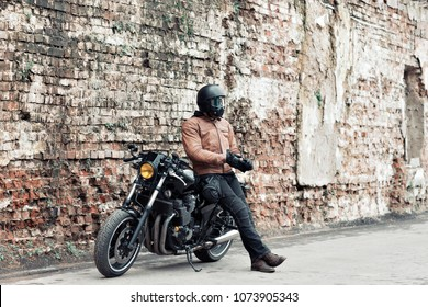 Man a motorcyclist standing with helmet near her bike, brick wall of garage background. Male in a leather jacket and tight pants
