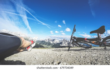 Man with mountain bike bicycle enjoying the view of Dolomites in a sunny day. POV Original point of view.