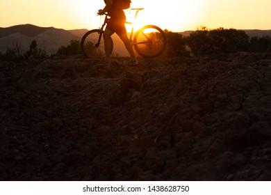 Man with mountain bike at sunrise