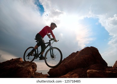 man mountain biking over extreme terrain