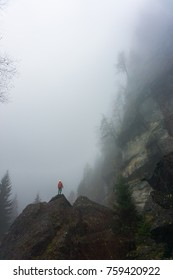 A man in a mountain scenery, with fog filling the valley and big walls. Tiny Human Lost In The Majesty Of Nature. Small man silhouette in the mountains. Foggy weather.