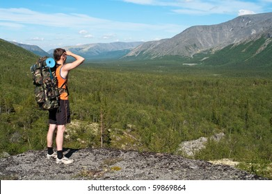 Man in mountain standing on peak of mountains and looking to far away