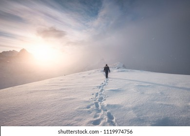 Man mountaineer walking with snow footprint on peak ridge in winter