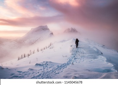 Man mountaineer walking with snow footprint on snow peak ridge in blizzard at morning
