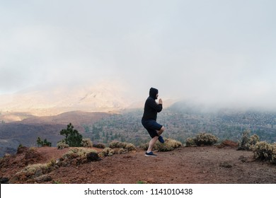 Man in the mountains doing yoga exercises