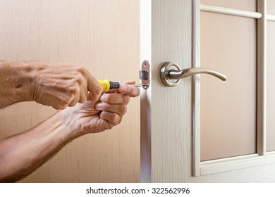 A man is mounting the protection strike of the deadbolt on a glass door with a modern curved style nickel handle using a screwdriver