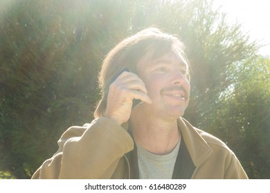 Man with moustache talking on smartphone