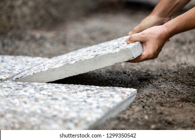 Man moves washed concrete slabs into a gravel bed, freshly laid path out of concrete slabs in the outdoor area
