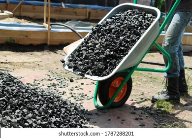 Man moving a wheelbarrow with crushed stones, as part of a building project