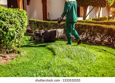 Man mowing the grass with a lawn mower by hotel. Worker cuts the lawn in summer garden wearing uniform.