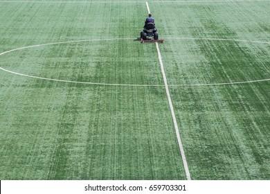 A man mowing the grass on a football stadium