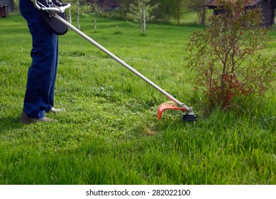 Man mowing grass with petrol weed trimmer.