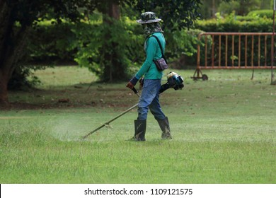 The man mowing green wild grass field using brush cutter mower or power tool string lawn trimmer