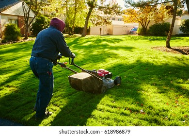 man mowing a lawn in the morning