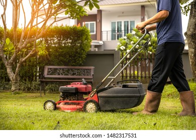 A Man mowing the lawn with red lawnmower at home  in summertime - closeup
