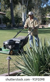 Man mowing yard of an upscale home