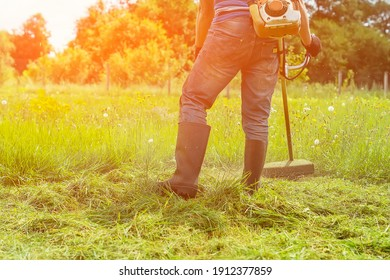 A man mows the grass with a hand-held lawn mower in the backyard in the sunlight. The gardener mows the long grass on the lawn in the garden with a trimmer. A farmer's lifestyle. Selective, soft focus