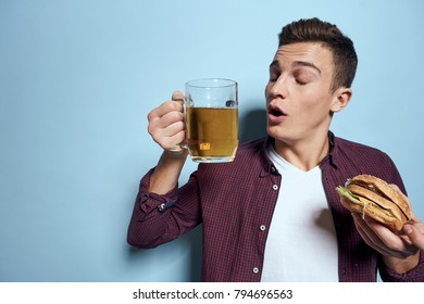 man with a mug of beer and a hamburger on a blue background