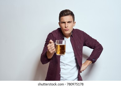 man with a mug of beer on a light background, alcohol, fun, male alcoholism