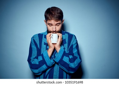 man with a mug of tea in a striped robe
