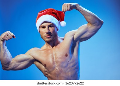 A man with muscles in his arms and a festive hat on his head