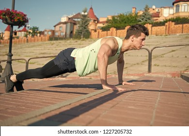 Man with muscular hands, biceps, triceps, strong muscles. Macho doing pushups on red brick stairs outdoors. Athlete in tracksuit on sunny summer day. Workout and training. Healthy lifestyle concept.