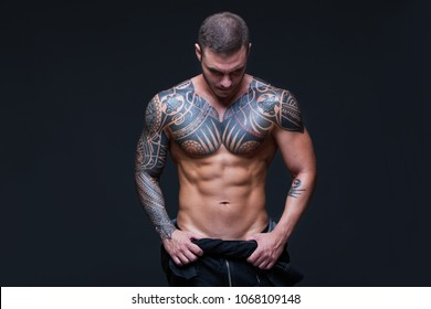 The man with a muscular naked torso with tattoos on the dark background. ABS