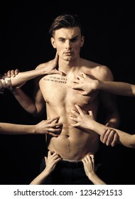Man with muscular torso, macho and many female hands, dark background. Macho on pensive face with muscular figure, enjoy female attention. Pheromones, desire and attraction concept