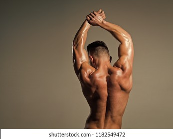 Man with muscular wet body and back. Athletic bodybuilder man on grey background. Dieting and fitness, healthy lifestyle. Sport and workout. Coach sportsman showing biceps and triceps, copy space