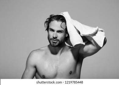 man with muscular wet body hold towel in bath or shower after washing in morning on grey background, hygiene and skincare, health and wakeup, everyday life, barbershop