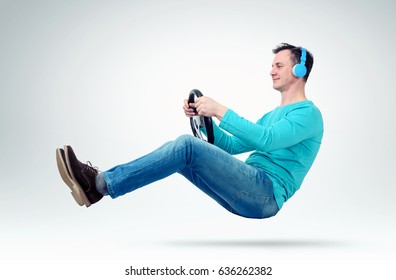 Man music fan in headphones drives a car with a steering wheel