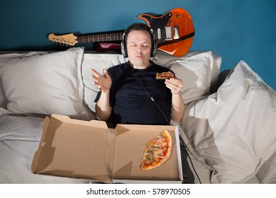 Man musician eating a slice of pizza and listens to music in studio. Unhealthy Lifestyle. Lunch break.