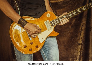 Man (musician, guitarist, rock, metall player or bluesman, blues performer) plays electric guitar. Leather wristband or bracelet with metal skulls on hand and jeans, only hands with guitar close-up