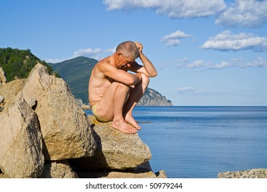 A man in musing on rocks at sea. Summer, sunny day.