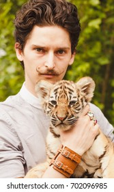 A man with a mustache looks into the face of a tiger cub