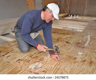 Man nailing down plywood sub-floor