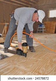 Man nailing plywood sub-floor with nail gun