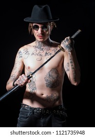 Man with naked tattooed torso in hat holding sword katana in hands on black background. Defense, honor, torture, punishment, harakiri concept.