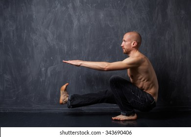 A man with a naked torso doing pistol squats on one leg