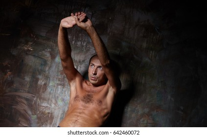 man with a naked torso on a dark background