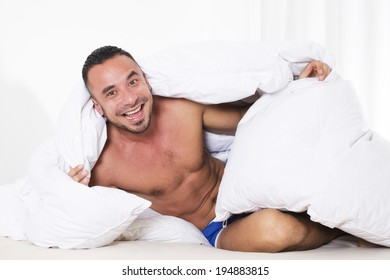 man with naked torso sitting in bed