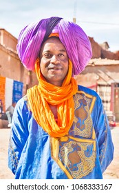 a man in national Berber clothing smiles against the background of the Moroccan villages