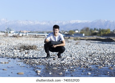 man in nature by the river with stones