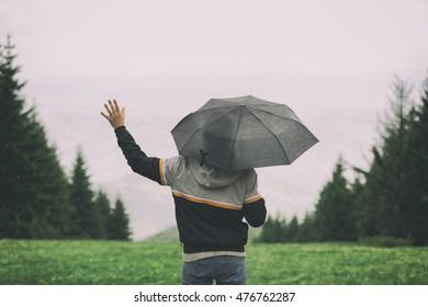 Man in nature holding umbrella.