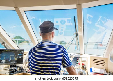 Man navigating a boat sitting in the captains chair during a cruise overlooking the ocean ahead, view from behind