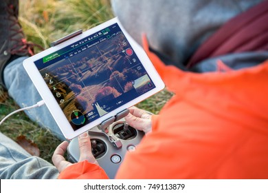 Man navigating a flying drone with remote control.Man in countryside flying drone and taking pictures.